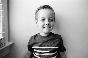 Black and white portrait of an adorable young boy smiling