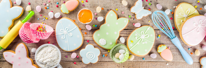 Easter cooking baking background with pastel colored easter cookies, sugar sprinkles and...