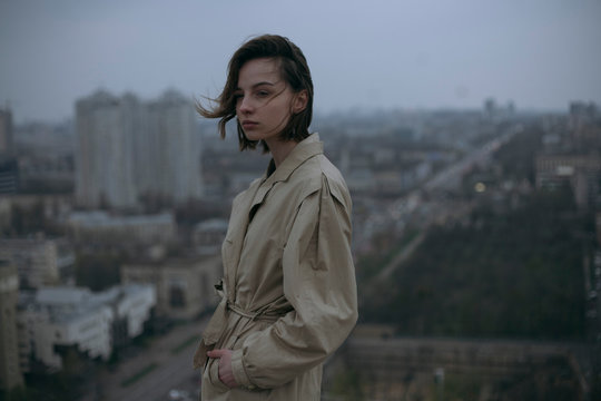 Thoughtful young woman in coat standing in city