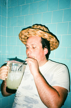 male with straw hat drinking cocktail from pitcher