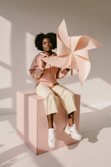 Cheerful black woman with pinwheel sitting on cube