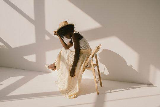 Stylish black female sitting near wall