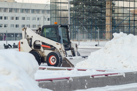 City municipal services are engaged in snow removal. Machines for cleaning snow. A tractor cleans the road from snow.