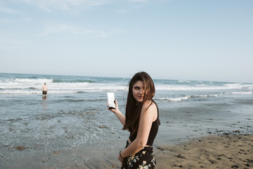 young woman taking pictures at beach
