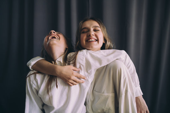 Sisters laughing indoors