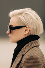 Portrait Of Young Blond Androgyne Woman with big sunglasses