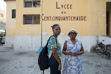 Student Kerlange Augustin and her mother pose for a photograph as schools and businesses tentatively reopen their doors, in Port-au-Prince