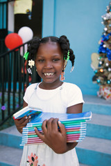 A student poses for a photograph while holding her new books, outside the College Saint Pierre-Eglise Episcopale D'Haiti, as schools and businesses tentatively reopen their doors, in Port-au-Prince