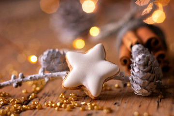 Closeup of homemade cinnamon cookie on rustic wooden table with bunch of cinnamon sticks  -  Christmas background, Advent bakery