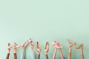 Many hands with different stylish shoes on color background