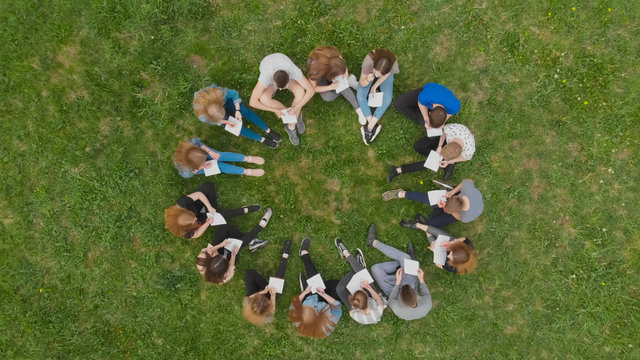A group of students are sitting in a circle and books on the grass.