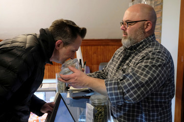 An employee holds a jar of marijuana on sale at the Greenstone Provisions in Ann Arbor