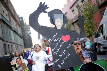 Woman holds up a cardboard figure with a picture of her missing daughter during a protest outside the National Palace in Mexico City