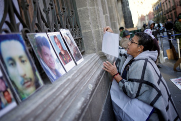 Woman places photographs of missing persons during a protest outside the National Palace in Mexico City