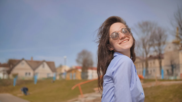 Beautiful 17 year old girl posing outdoors against the blue sky.