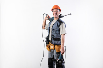 Fototapeta A builder with a hammer drill on his shoulder, and a angle grinder in his other hand, in a helmet, smiles. obraz