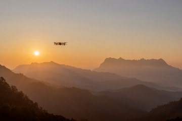 The drone with the professional camera takes pictures of the misty mountains at sunset.