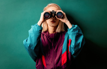 Style woman in 90s punk clothes with binoculars on aqua menthe color background