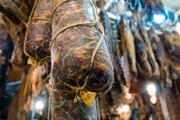 Homemade dry salami - traditional meat products, by smoked pork hanging in smokehouse ready for sale at winter Christmas market