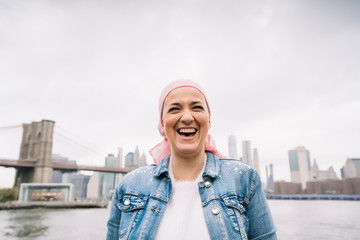 Portrait of laughing woman with cancer bandana at Brooklyn Bridge in New York, USA
