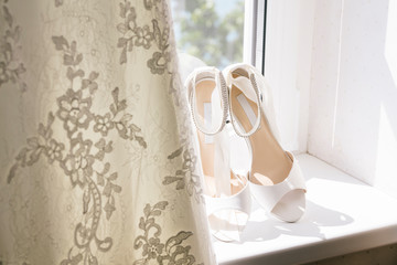 Close-up of wedding sandals by dress on window sill at home