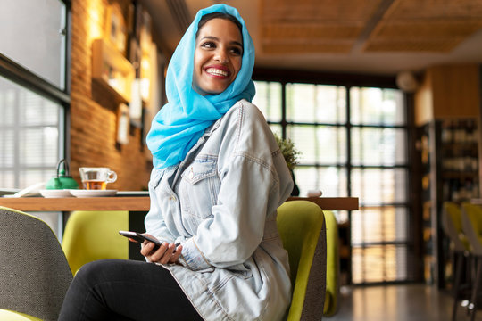 Young woman in hijab sitting with smartphone in cafe