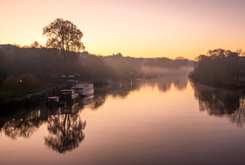 Beautiful landscape of Thames river early in the morning illuminated by colorful sunrise reflected in the foggy surface of water in London