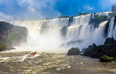 Touristic boat heading towards the powerfull stream of Iguazy Falls panorama, Puerto Iguazu Argentina