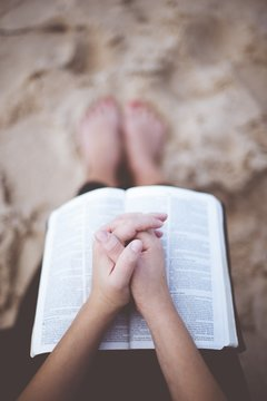 Vertical shot of a person praying with their hands on the bible