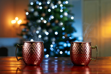 Close-up of mulled wine served on wooden table against illuminated Christmas tree at home