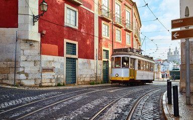 Lisbon, Portugal. Vintage yellow retro tram on narrow bystreet tramline. Red houses in Alfama district of old town. Popular touristic attraction of Lisboa city. Wall mural