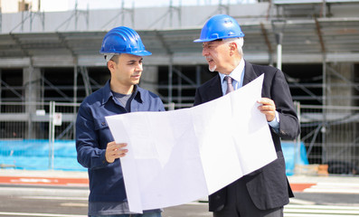 Fototapete - Two architect developers reviewing building plans at construction site