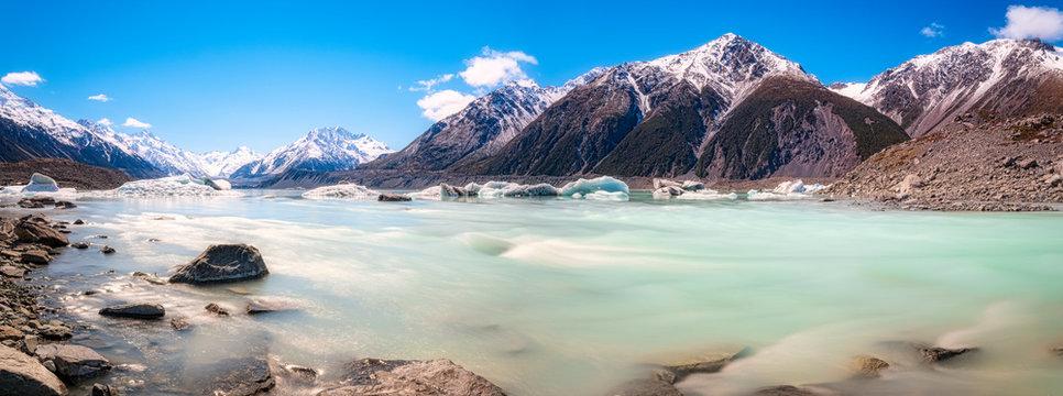 New Zealand, South Island, Rocky shore of Tasman Lake with icebergs, glacier and mountain backdrop