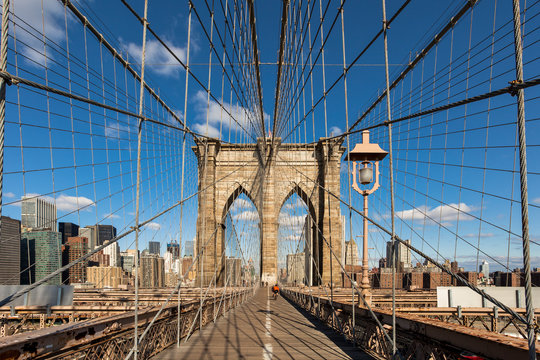 Diminishing perspective of Brooklyn Bridge against blue sky in New York City, USA