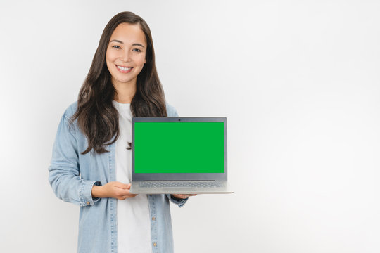 Happy asian woman holding laptop with empty chroma key screen over white background