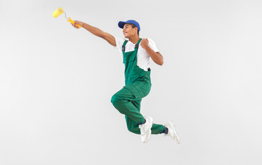 Jumping African-American decorator on white background