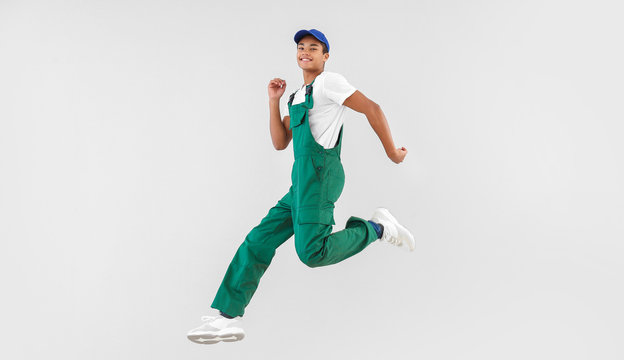 Jumping African-American teenager boy in uniform on white background