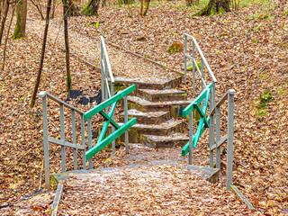 Footbridge over the ravine in the autumn city Park