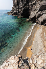 A young woman walks along a wonderful and lonely beach with transparent waters on the Mediterranean coast in Spain, near the small town of Cabo de Palos, Cartagena