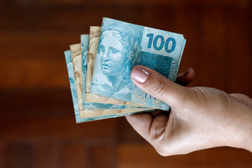 Hands holding Brazilian real notes - Money from Brazil - Notes of Real - Brazil BRL banknote Fototapete