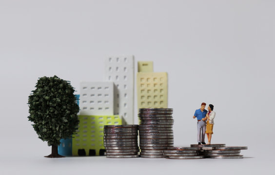 A miniature couple on pile of coins with miniature tree and miniature building.