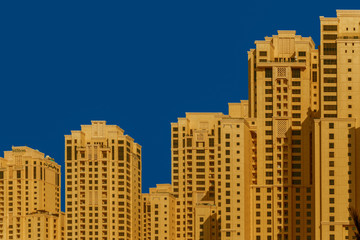 Modern skyscrapers of the fast-growing city. classic blue sky