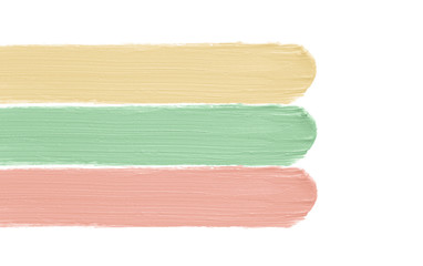 Color corrector strokes isolated on white background. Green peach yellow color correcting concealer cream smudge smear swatch sample. Makeup base creamy texture