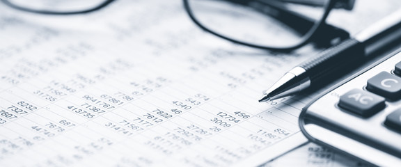 Close-up Pen Calculator And Reading Glasses On Financial Report - Business Accounting Concept