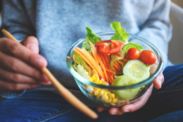 Closeup image of a woman eating and holding a bowl of fresh mixed vegetables salad by fork