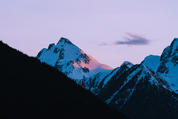 Foto auf Leinwand Flieder Pink and orange last light on snow covered mountains during sunset in winter in Canada