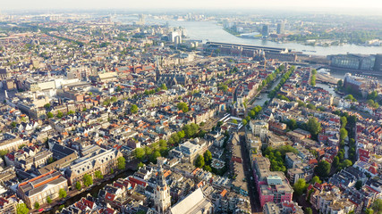 Amsterdam, Netherlands. Flying over the city rooftops towards Amsterdam Central Station ( Amsterdam Centraal ), Aerial View