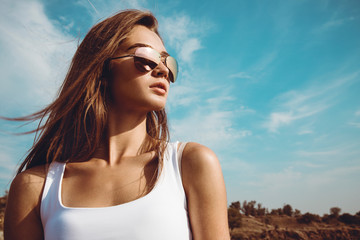 Beautiful girl in a white shirt and classic aviator sunglasses posing in the desert during the sunset. Outdoor shot. Summer vacation concept.