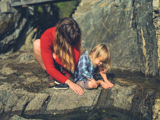 Mother and toddler studying rock pool