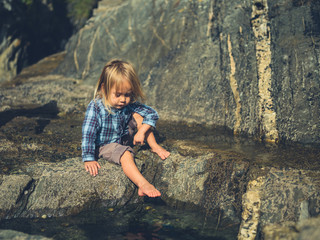 Little toddler dipping his feet in rock pool